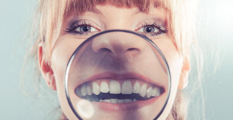 Vrouw met vergrootglas voor mond