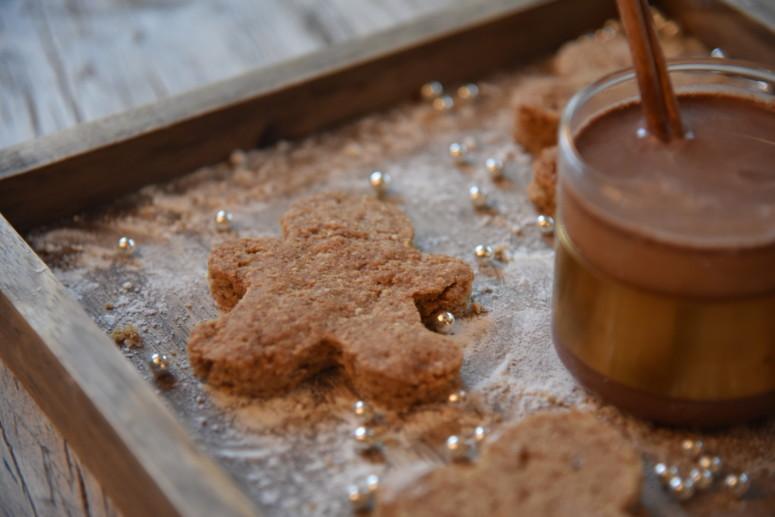 Koekjes in de vorm van mannetjes op plateau met warme chocolade melk
