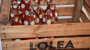 Een houten krat met rode flessen van Lolea